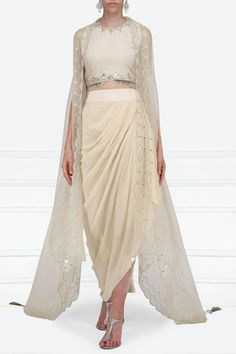 Priyanka Singh Featuring a beige crop top in georgette base with pearls, sequins and stones hand embroidery. It is paired with a matching drape skirt in crepe base and an asymmetrical embroidered organza cape with scallop edging. Indian Wedding Outfits, Indian Outfits, Drape Skirt Pattern, Indian Crop Tops, Mehendi Outfits, Indian Gowns Dresses, Dress Indian Style, Draped Skirt, Indian Designer Outfits