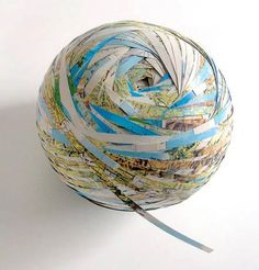 Map of the world cut into thin strips and rolled up into a ball. Interesting decorative piece.