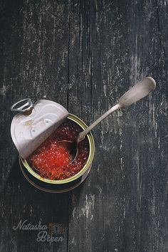 Red Сaviar - Open Tin with red caviar and silver spoon over wooden surface. Dark rustic style. Top view.