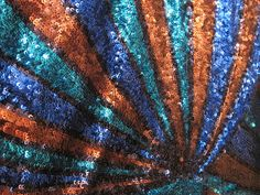 54 wide    Priced per yard.    Various blues and brown sequins sewn in a geometric print on a heavy mesh.