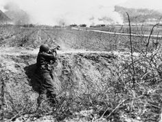 Pfc. Karl Klein, Seattle, Wash., automatic rifleman of the U.S. 7th Div, makes sure that the reds leave this burning Korean village in only one direction to the rear on April 26. The GI fires into X Youchon, on Korea's western front, where allied troops were slowly retreating under pressure of a 300,000 man communist force driving towards Seoul.