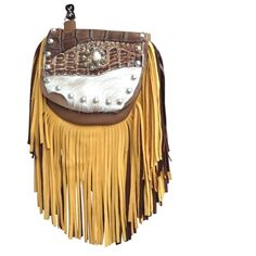"""SUNKISSED GATOR MARTY - made of soft brown deerskin with a 7"""" gold and chocolate brown deerskin fringe. The flap features genuine alligator and hair-on-hide. The centerpiece is a silver and gold metal concho with a pair of dueling six shooters on it. Etched silver metal studs outline the flap. Wear bag clipped to belt loops for hands-free carrying of your essentials. Interior includes a leather strap. Add the strap when you want a completely different look."""