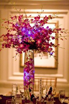 Gorgeous Centerpiece! We don't want to go tall, but I love the idea of having that purple/pink LED light in the middle of the bunch of orchids...we may be able to do this in the globe idea.
