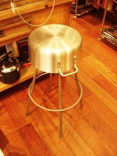 Recipiente metálico convertido en el asiento de un taburete.