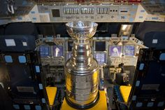 In Orbiter Processing Facility-2, Lord Stanley's Cup sits in the flight deck of space shuttle Atlantis, on January 18, 2012. The Stanley Cup was awarded to the Boston Bruins after winning the 2011 National Hockey League Championship. Jeremy Jacobs, chairman and chief executive officer of Delaware North Companies and owner of the Boston Bruins, had brought the cup to Florida for Kennedy and Delaware North employees to view and take photographs. (NASA/Kim Shiflett)