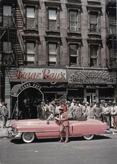 Boxer Sugar Ray Robinson leaning on his 1950 pink Cadillac convertible in front of two of his businesses (including restaurant) in Harlem St.) // (Photo by George Karger/Pix Inc.