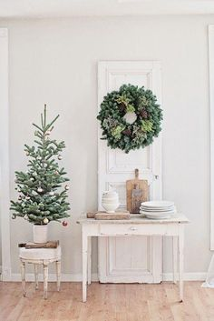 Beautifully styled shot with mini-Christmas tree and wreath adding the festive style Anthropologie Ornaments -- a great holiday decor idea without using any red! We love the natural whites and neutrals with green pine tree and boxwood wreath.