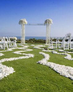 Great use of white flowers! Beautiful archway and interesting aisle at this ceremony site overlooking the ocean. #wedding #beach