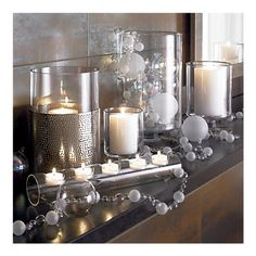 modern christmas mantle with glass hurricanes