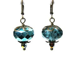Sparkling vintage style dangle earrings featuring large and lovely sparkling 9x14 mm Czech glass beads in stunning metallic aqua marine. The beads are coupled with faceted fire polished AB Czech glass rounds in light aqua and antiqued brass bead caps. Earrings dangle approximately 1.5 inches (38.1mm) from the tops of the lead and nickel safe antiqued brass lever back ear wires.  More jewelry by NaLa: http://jewelrybyNaLa.etsy.com How to Buy on Etsy: http://www.etsy.com/help/article/339