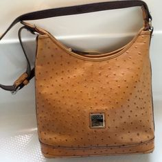 Tan Ostrich Leather Dooney & Bourke Like brand new.. Metal protection stands on bottom.No signs of wear, stains or imperfection on outside. Leather inside, 2 very small marks on the bottom of purse. Very classy, dress up or down Dooney & Bourke Bags Shoulder Bags