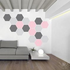 Hexagon wall decals of various shades of grey and a shade of pink placed in a honeycomb pattern on a white wall behind a dark grey modern couch and a chic coffee table.