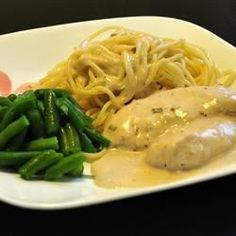 Chicken breasts cook gently in a creamy sauce of cream cheese, golden mushroom soup, Italian dressing mix, and white wine in this easy slow cooker recipe.