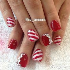 Red and white Christmas nail art theme. Make your nails your very own candy cane with the red and white striped combination. Add embellishments on top for more effect.