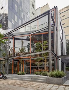 This modern coffee shop in Vietnam has double height windows, a garden and multiple seating areas. #ModernCoffeeShop #CoffeeHouse