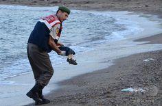 シリア難民の子供の遺体を抱く警官