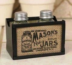 """Burlap Salt and Pepper Caddy - Mason Jars Logo Box of 2    Metal caddy with glass on both sides measures 4½"""" wide, 3"""" tall, and 3"""" deep.     Glass is covered in burlap and printed with ink that is waterproof and permanent.     Includes recycled glass mason jar salt and pepper shakers.     Please wash before use with food."""