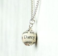 """This beautiful necklace features a wooden bead covered with pages from Jane Austen's """"Pride and Prejudice"""""""