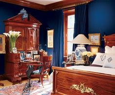 Ralph Lauren's Bedford Beauty: The master bedroom, which is enveloped in a deep-blue fabric, is anchored by a Georgian mahogany-and-walnut bureau-cabinet and an 18th-century mahogany armchair by Georges Jacob. A Regency bed, chinoiserie accents and Oriental rugs round out the mix of styles.