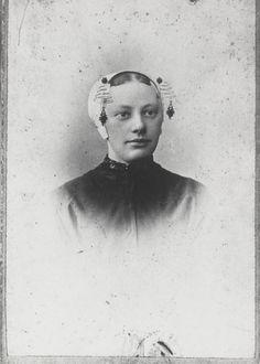 Vrouw in Vlaardingse dracht. de vrouw draagt de zogenaamde 'korte kap'. Aan de krullen van het oorijzer hangt een paar oorijzerhangers. 1890-1905 #ZuidHolland #Vlaardingen