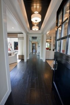 So cool! I love the framed in dark wood on the ceiling with all of the white trim and dark floors