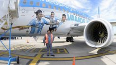 A worker poses next to the airliner dacorated with the portraits of Argentina's National team footballers.