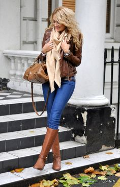 Brown leather jacket, light brown scarf, brown handbag, blue skinny jeans, and brown boots.
