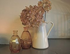 hydrangeas in a metal pitcher with rose colored vases