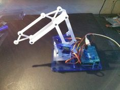 This is the first iteration of the Me-Arm project. The objective is to build a very low cost robot arm for use in everyday tinkering and education. The BOM is a handful of M3 fixings, an A4 sheet of acrylic and 4 x 9g hobby servo motors. The idea being that it is simple to build and the most vulnerable parts are cheaply replaced.   Inspiration came from the U-Arm kickstarter but the starting parts have more in common with the construction and simplicity of the Plot Clock.