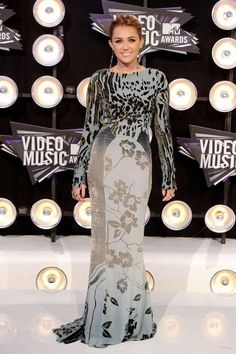 Miley Cyrus making her first appearance at the MTV Video Music Awards in a Roberto Cavalli gown. See all of the singer's wild looks.
