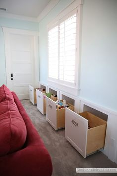 Organized playroom!  A room designed with toy organization in mind.  These extra large drawers look like part of the wainscot but actually pull out for more hidden toy storage!  (Sunny Side Up)