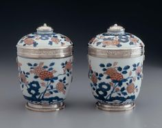 One of a pair of Japanese Imari silver-mounted covered jars, the porcelain painted with chrysanthemums and foliage in blue and red with gilding. The mounts on the body comprising a circular gadrooned foot, four rosette bolts, and a collar of engraved strapwork. On the lid, a molded rim and round domed knob with band of engraved strapwork.