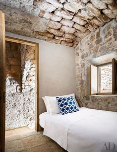 Rustic stone walls add historic and romantic flair to this bedroom architect Steven Harris and interior designer Lucien Rees Roberts's retreat in Croatia. | archdigest.com