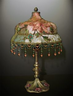 Heavy antique lamp base circa 1920 has painted lilies in the base. Shade is Minuret style dyed pink and blue than gilded with a layer of antique gold metallic lace with a large colorful Chinese embroidered applique of a lily wrapped around it. Fanciful hand beaded fringe has pink flower end drops.
