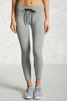 A pair of knit leggings featuring contrast drawstrings, seam-stitched panels, and an elasticized waist.
