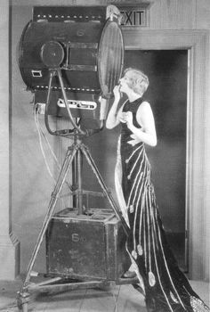 """preparing to go in front of the camera.mgm star gwen lee uses a reflector as a mirror while she appklies her make-up,1929."""
