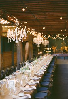 large harvest table and chandeliers reception. Love the navy chair cushions combined with the rustic runner--
