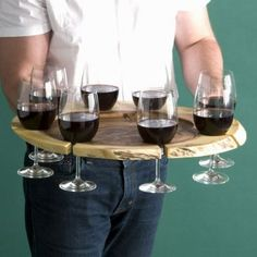 Very cool idea - looks like there's a hole where the glasses set a bit down so they can't slide out.  Nice way to carry filled wine glasses so they won't slide around or tip over. Or, if it is supported and set up like a tall lazy susan you could put little name cards by the slots for parties, no coasters, no rings, no spilled drinks!