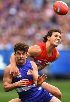 #AFLGF2016 Tom Liberatore of the Bulldogs handballs whilst being tackled by Kurt Tippett of the Swans during the 2016 AFL Grand Final match between the Sydney...