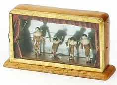 "Encased Peg Wooden Miniature Theater : Lot 11 England, ca. 1840, wooden case with glass front contains 4 fully jointed peg wooden dolls in front of mirrored back  Size: case 2"" t."
