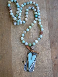"""Rustic heart long necklace She Loves Bohemian by 3DivasStudio-  This boho chic necklace features a hand forged heart pendants on a long strand of sky blue faceted natural amazonite stones. It's embellished with a tiny tie of soft deerskin lace and topped with a rhinestone barrel. Given an aged patina for a wonderful """"old world"""" look and feel... The knotted strand is approximately 26 inches.  Pendant is approximately 1 inch X 2 inches. Slip it over your head and go :)"""