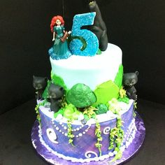 Brave birthday cake, purple plaid edible image wrap, buttercream iced, icing bushes and vines, chocolate trees, and toy figurines.