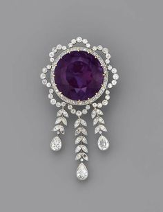 A Belle Epoque amethyst and diamond brooch, circa 1900. Photo Christie's Image Ltd 2006  The circular-cut amethyst within the diamond garland surround, suspending a graduated fringe of diamond leaves to the three pear-shaped drops, millegrain setting, mounted in platinum and gold
