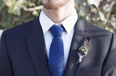 stylish groom's attire, love the feather bout!