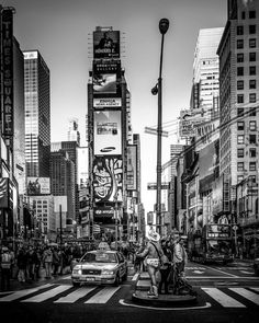 Time Square NYC. I remember that I took this photo between two flights and I was with my daughter it was the first time she was in New York and all those buildings were very impressive it was very alive with the naked cowboy singing in the middle a pretty funny scene. But I like it in black and white it almost looks like time stopped for a second.  #photoserge #blackandwhite #travel #art #fineart #NYC #walkinginNYC #NewYork #nakedcowboy #instagood #photooftheday