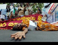 A Tamil woman cries as she holds up an image of a family member who disappeared during the war against Liberation Tigers of Tamil Eelam  (LTTE) at a protest in Jaffna, Sri Lanka, Aug. 27, 2013. (Dinuka Liyanawatte/Reuters).