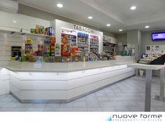 Banco tabacchi e ricevitoria dalle linee moderne ed essenziali in laminato bianco lucido con inserti metallici. Tabaccheria allestita in provincia di Torino.