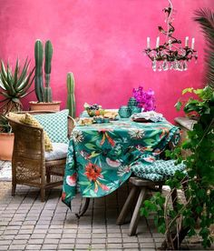 A colourful Morrocan style patio, but it could equally work in a garden room. Shocking Pink walls, tropical print table cloth, chandelier and indoor plants. Bring in the sunshine and recreate the ultimate idyll with these ideas