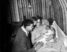 Joseph and Winifred Roderick and their daughter Doreen, pose for the press with their new arrival, baby Peter Roderick, the first baby recorded to have been born in an air-raid shelter during the London Blitz. 1943