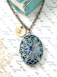 A romantic and antique style personalized locket necklace with your choice of initial. The antique brass locket is hand painted patina, buffed and sealed to give it an antique look. A blue cubic zirconia crystal lays on the front of the locket gives this locket a sparkle in the light. Make it your own with a hand stamped initial on a rustic 24K gold plated round tag.  Necklace chain is a solid quality antique brass rolo chain. #locket #necklace #jewelry